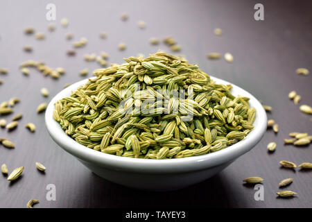 Fennel seeds in a bowl on a wooden table - Stock Photo