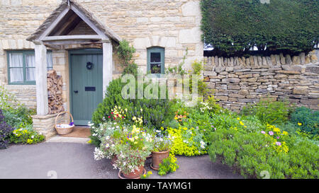 Front garden with vibrant flowers in bloom, lush herbs by a stone cottage in an english rural village. - Stock Photo