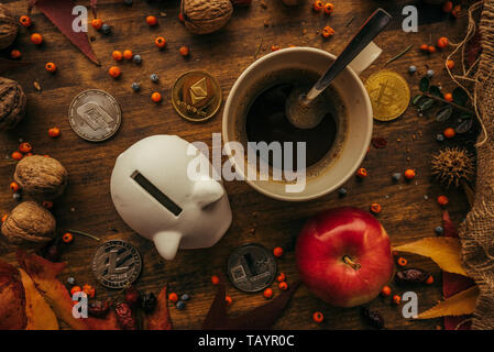 Piggy coin bank and cryptocurrency coins on table with autumn season edcoration arrangement, top view flay lay retro toned digital wallet concept - Stock Photo