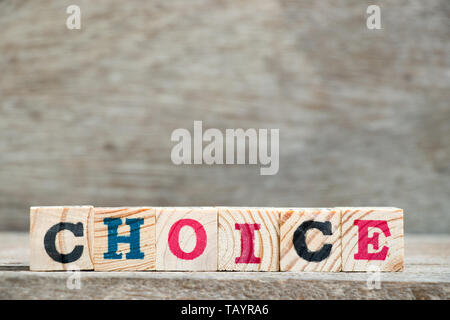 Letter block in word choice on wood background - Stock Photo