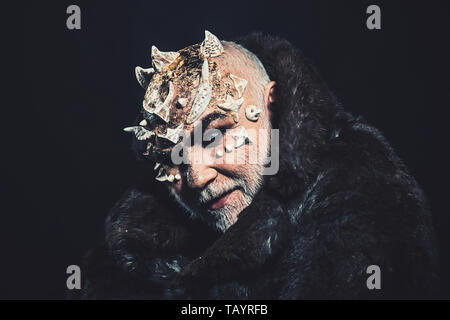Alien, demon, sorcerer makeup. Horror and fantasy concept. Man with thorns or warts in fur coat. Demon on black background, copy space. Senior man wit - Stock Photo