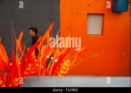15.03.2019, Singapore, , Singapore - A man walks past an orange house wall in Chinatown. 0SL190315D011CAROEX.JPG [MODEL RELEASE: NO, PROPERTY RELEASE: - Stock Photo