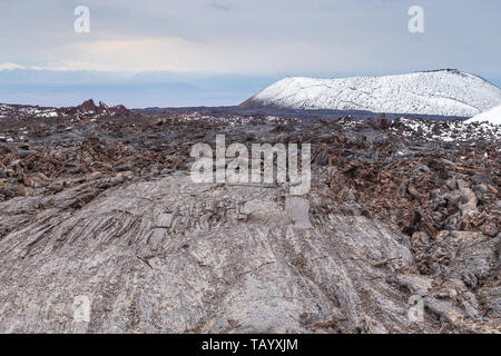 Bizarre formation on fresh lava field. Snow- capped mountain in the background. Volcanic complex on Kamchatka Peninsula in the far east of Russia. - Stock Photo