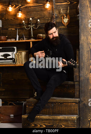 Boost your skills. Guy in cozy warm atmosphere learn new song chords. Man bearded musician enjoy evening rehearsing performance at home, wooden backgr - Stock Photo