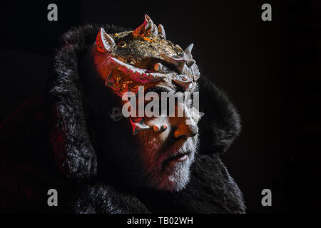 Wizard with thorns on face standing in darkness, nightmare concept. Demon in fur collar on white background. Man with white beard and creative makeup - Stock Photo