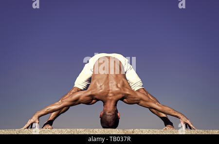 Yoga practice helps find harmony and balance. Man practicing yoga blue sky background. Reached peace of mind. Meditation and yoga concept. Yoga helps find balance. Practice asana outdoor. - Stock Photo