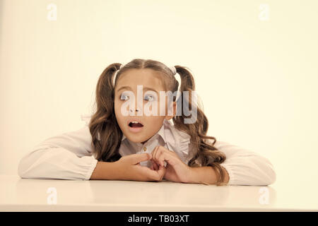 Pupil lean desk isolated white. Perfect schoolgirl tidy fancy hair. School as stranger environment. Prepare kid first school day. Schoolgirl stressful scared worrying face. Stressful event for her. - Stock Photo