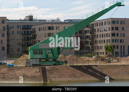 An old harbor crane for smaller ships on the shores of an inland port of new housing estates in Mainz. - Stock Photo