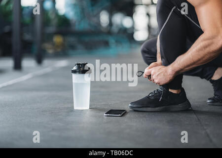 Man tying shoe laces on sneakers in gym - Stock Photo