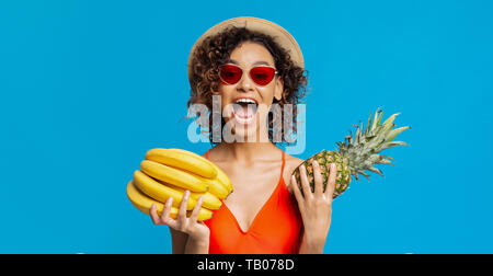 Emotional black girl holding bananas and pineapple - Stock Photo