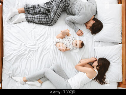 Little baby lying in the middle of bed, parents sleeping on sides