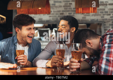 Friends Meeting. Men Drinking Beer And Talking In Bar - Stock Photo