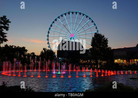 Ferris wheel and water fountain with colored lights at dusk - Stock Photo