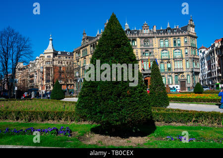 Bilbao, Spain. February 15, 2019. Pine tree at Moyua Square (Plaza Moyua). Chavarri Palace in the background - Stock Photo