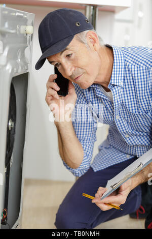male technician on the phone checking a machine - Stock Photo