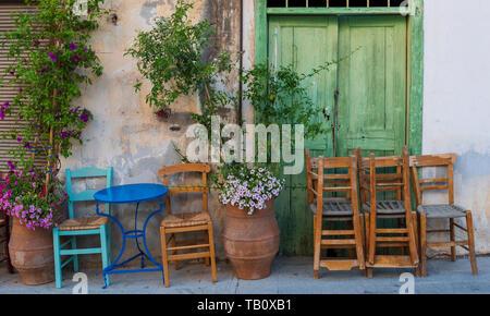 Stacked chairs outside Greek street cafe, Agio Nikolaos, Crete - Stock Photo