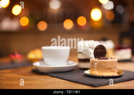 Fresh chocholate cake with sweet biscuit on top in a coffee shop. Sweet mini cakes over a wooden table in a coffee shop. Tasty desserts. Coffee shop specialities. - Stock Photo