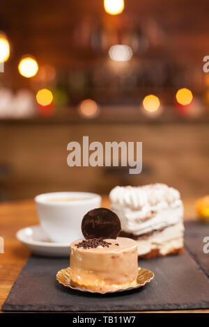 Close up photo of delicious chocholate cake with tasty biscuit on top. Tasty mini cakes in a coffee shop. Traditional desserts. - Stock Photo