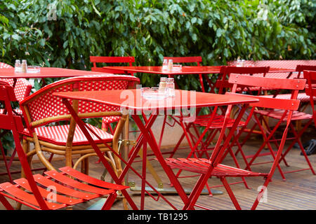 Outdoor restaurant red tables and chairs in summer - Stock Photo