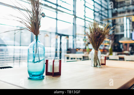 Empyu shopping center cafe interior design. Table decorated with vases full of dry glass with candles. - Stock Photo