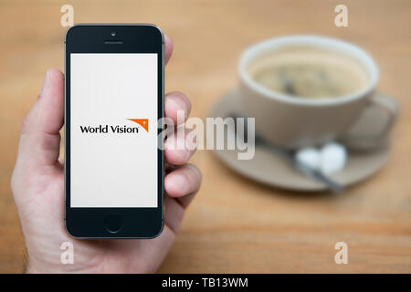 A man looks at his iPhone which displays the World Vision logo (Editorial use only). - Stock Photo