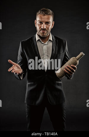 Restaurateur holding vintage bottle. Sommelier with good wine. Bearded man wearing dark suit and white shirt. Macho with confident look isolated on black background. Party concept, social drinking. - Stock Photo