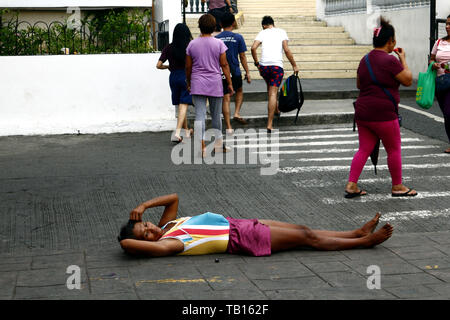 ANTIPOLO CITY, PHILIPPINES - MAY 21, 2019: A homeless woman lies down on the street outside of a church where she asks for alms from passers by. - Stock Photo