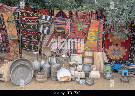 Old carpets, metal jugs, wooden barrels and other kitchen utensils are sold at a flea market in Tbilisi, Georgia - Stock Photo