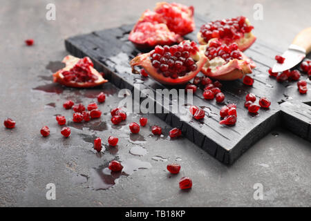 Wooden board and pieces of ripe pomegranate on grey background - Stock Photo