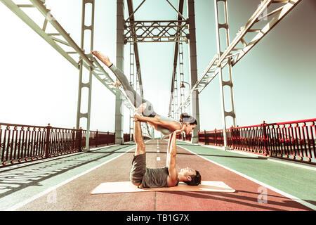 Young couple practicing acroyoga outdoors on the bridge - Stock Photo