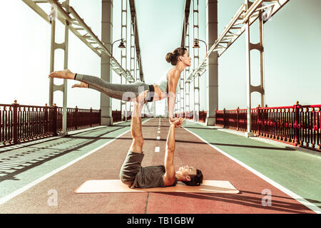 Attractive young couple doing an acroyoga front plank pose - Stock Photo