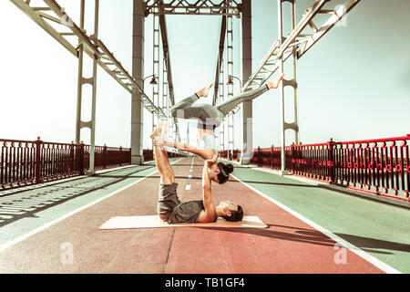 Young yogi on a mat holding his partner - Stock Photo