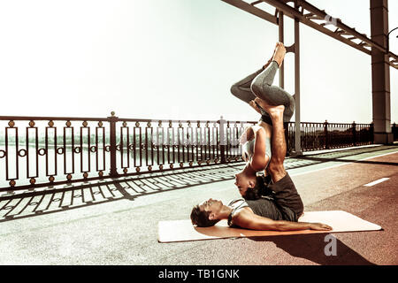 Young couple doing acroyoga on an exercise mat - Stock Photo