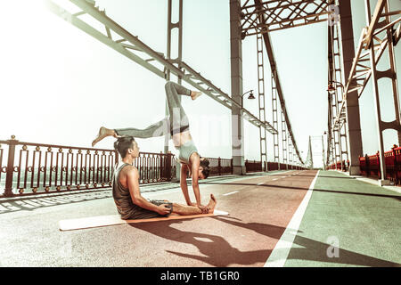 Yogi doing a handstand supported by her male partner - Stock Photo