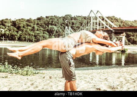 Young people practicing acroyoga on the beach at sunrise - Stock Photo