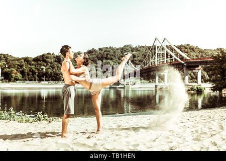 Female yogi leaning on her partner while stretching - Stock Photo