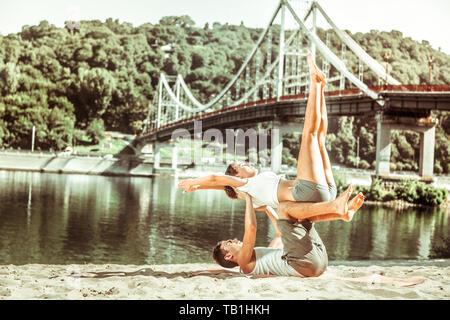 Yogi on an exercise mat balancing his partner - Stock Photo