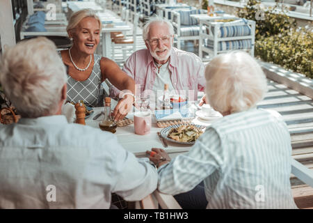 Positive delighted mature people talking during dinner - Stock Photo