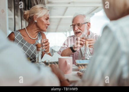 Cheerful elderly couple having dinner with their friends - Stock Photo