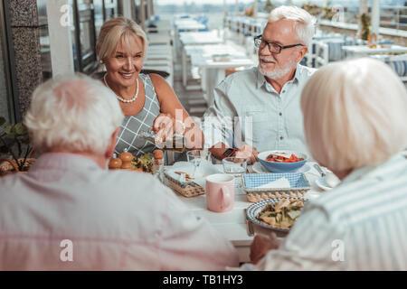 Positive delighted elderly couple having dinner outside - Stock Photo