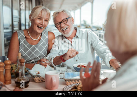 Positive delighted couple communicating with their friends - Stock Photo