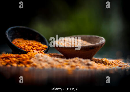 Close up of raw pink lentils in a clay bowl on wooden surface with its powder. - Stock Photo
