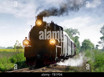 Old passenger train running on tracks through the forest. Retro locomotive with a steam engine, smoke and big lamps. - Stock Photo
