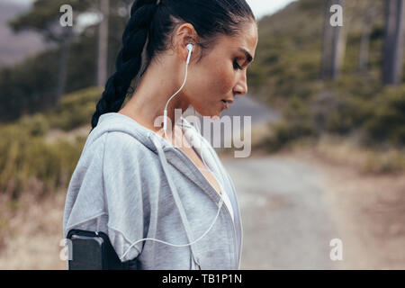 Side view of a female athlete wearing earphones. Woman listening to music during workout outdoors in morning. - Stock Photo