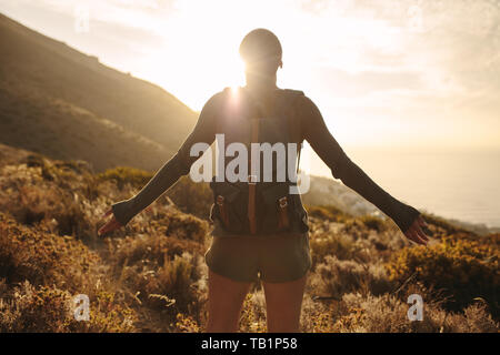 Rear view of woman with backpack standing on country path looking at the sun with her hands outstretched. Female hiker embracing the sun light.