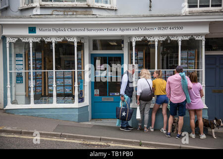 Family looking at properties for sale advertised in an estate agent window in West Dorset, England, United Kingdom - Stock Photo