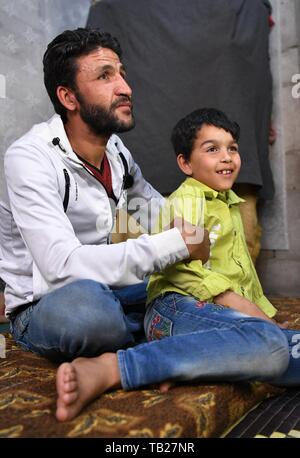 Damascus, Syria. 28th May, 2019. Hussain Mossa (L) sits with his son Ibrahim in their unfinished house in the Jaramana suburb of Damascus, Syria, on May 28, 2019. For Hussain Mossa, whose childhood was peaceful and worth remembering, his son Ibrahim is not so lucky as him. Hussain's older son, Ibrahim, was born in 2011 when the Syrian crisis began. In Syria, those who were born during the war were regarded as 'Generation of War.' They were unable to have a normal or healthy childhood like many of their parents did. Credit: Ammar Safarjalani/Xinhua/Alamy Live News - Stock Photo