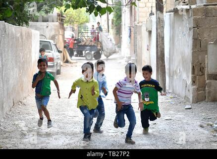Damascus, Syria. 28th May, 2019. Ibrahim Mossa (2nd L) plays with his siblings and cousins near their rented house in the Jaramana suburb of Damascus, Syria, on May 28, 2019. For Hussain Mossa, whose childhood was peaceful and worth remembering, his son Ibrahim is not so lucky as him. Hussain's older son, Ibrahim, was born in 2011 when the Syrian crisis began. In Syria, those who were born during the war were regarded as 'Generation of War.' They were unable to have a normal or healthy childhood like many of their parents did. Credit: Ammar Safarjalani/Xinhua/Alamy Live News - Stock Photo