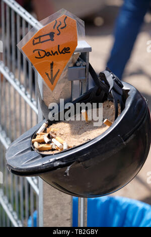 An old riding helmet with sand and cigarette ends in it is being used as an ashtray with a sign saying 'Danke' (thanks) - Stock Photo