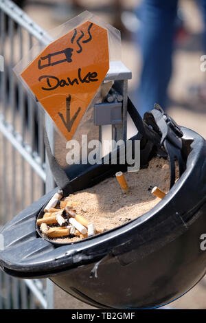 An old riding helmet with sand and cigarette ends in it is being used as an ashtray with a sign saying 'Danke' - Stock Photo